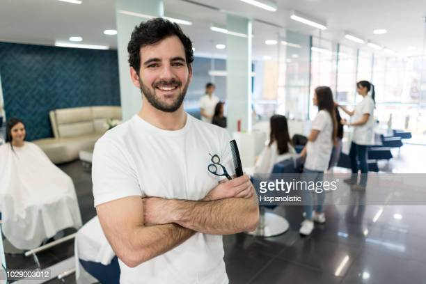 professiona male hair stylist at his business looking at camera smiling with arms crossed while holding scissors and a comb - parrucchiere foto e immagini stock