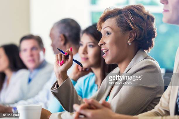 Professional African American businesswoman asking question during business conference