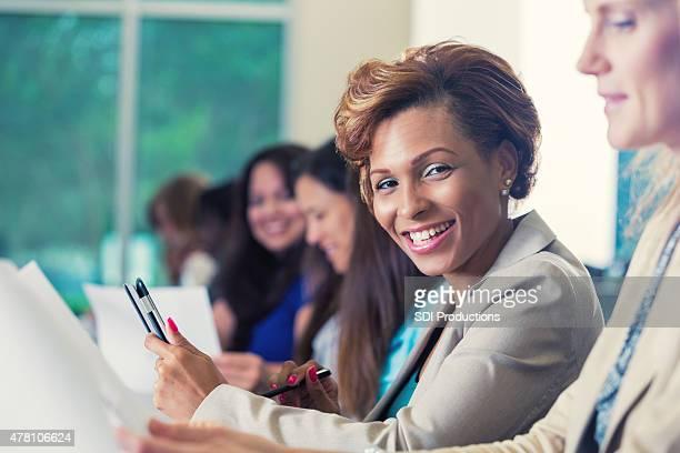 Profesional afroamericana empresaria está sonriendo durante una conferencia de negocios