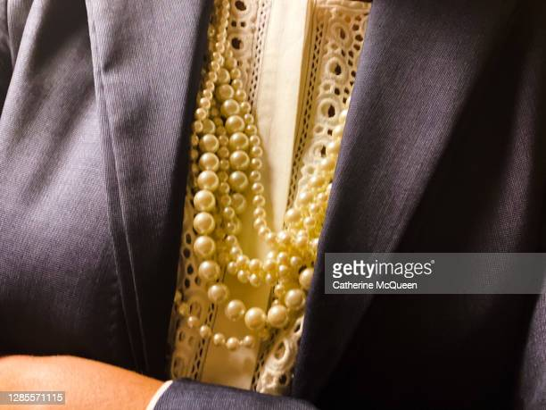 professional african-american woman dressed in smart navy work blazer & pearls with arms crossed - member of congress stock pictures, royalty-free photos & images