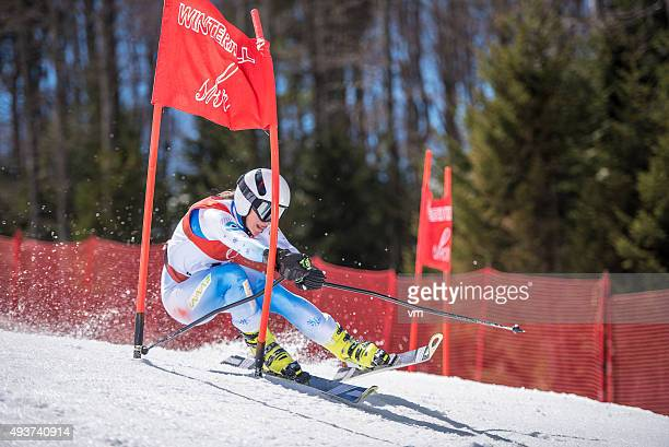 professional alpine skier in low stance taking sharp carving turn - alpine skiing stock pictures, royalty-free photos & images