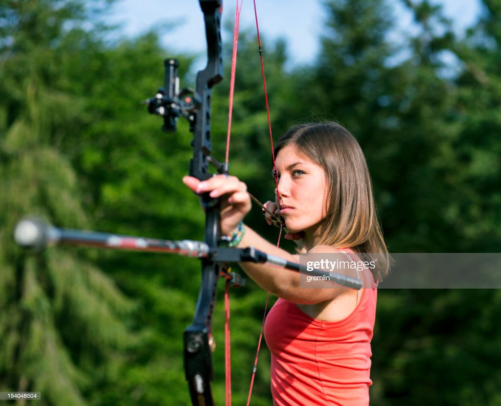 Professional archer aiming in position : Stock Photo
