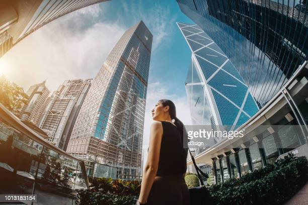 professional asian businesswoman standing against highrise financial towers in central business district and looking up into sky with confidence - central stock pictures, royalty-free photos & images