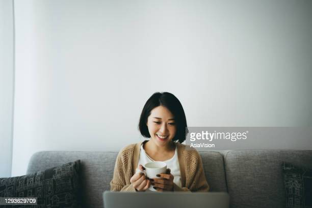 professional asian young woman using her laptop to do her work at home during the pandemic time - east asian ethnicity stock pictures, royalty-free photos & images