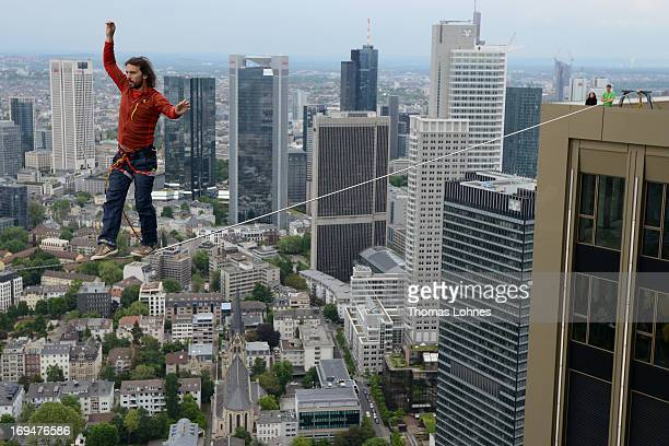 Professional Austrian slackliner Reinhard Kleindl walks along a 30 metre long cable suspended 185 Meters from the skyscraper PwC on May 25 2013 in...