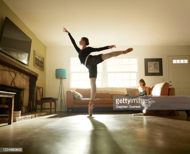 professional ballerina is executing an arabesque in her parents home on point - バレリーナ ストックフォトと画像