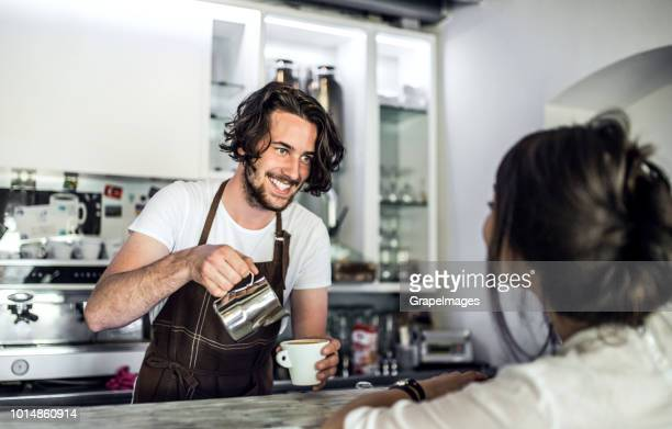 A professional barista working in a cafe, preparing coffee for a female customer.