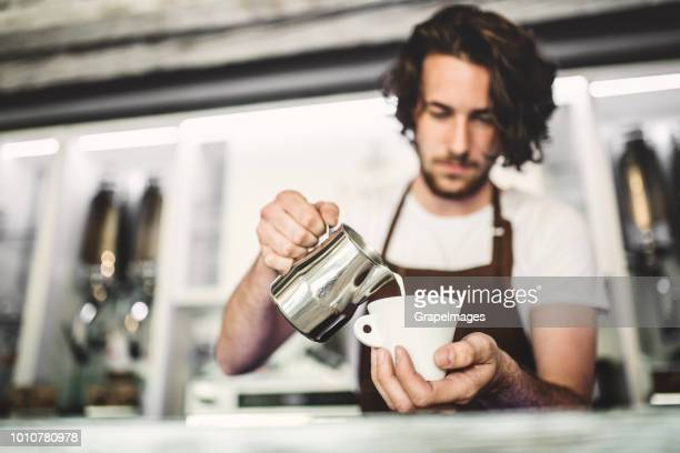 A professional barista working in a cafe, preparing coffee.
