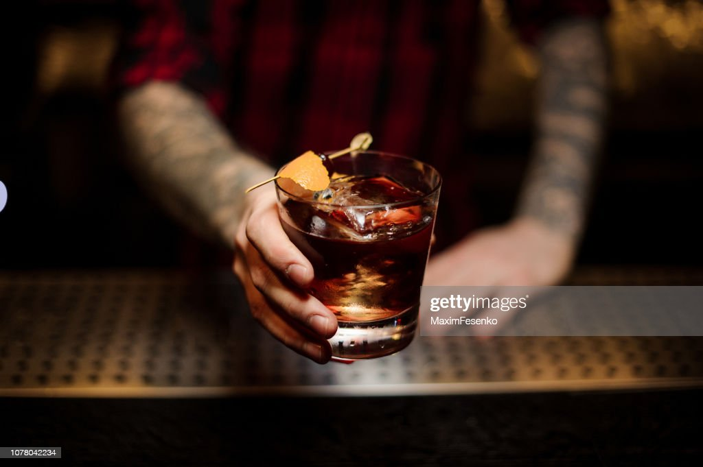 Professional bartender serving a delicious Godfather cocktail : Stock Photo