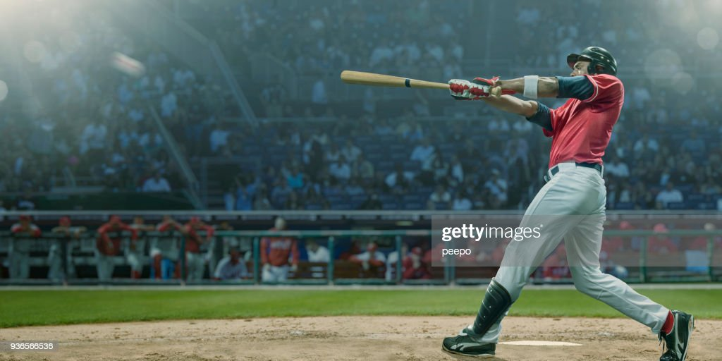 Professional Baseball Player Hits Ball In Mid Swing During Game : Stock Photo