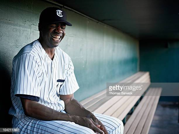 Professional baseball player laughing in dugout