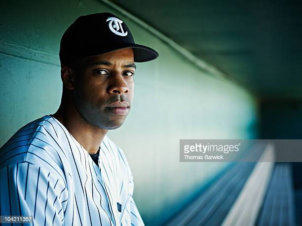 Professional baseball player sitting in dugout