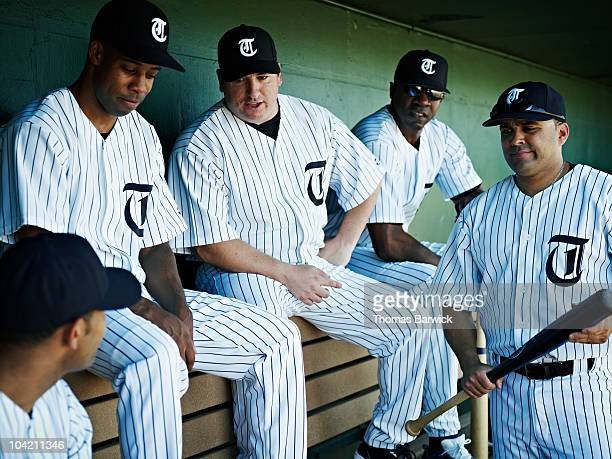professional baseball players in dugout - baseball uniform stock pictures, royalty-free photos & images