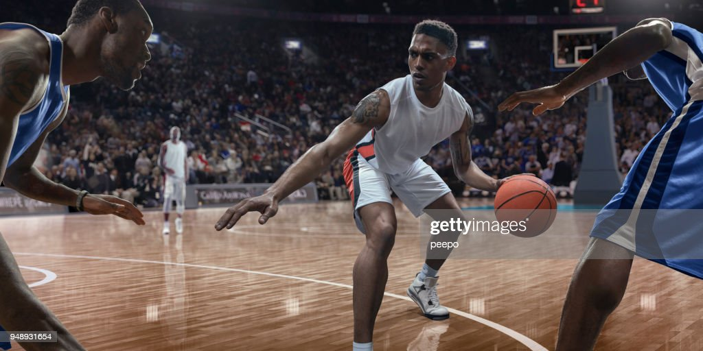 Professional Basketball Player Dribbling Ball Near Opponents During Game : Stock Photo