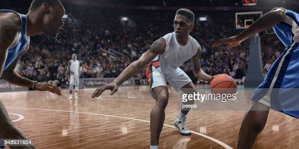 professional basketball player dribbling ball near opponents during game - bouncing stock pictures, royalty-free photos & images