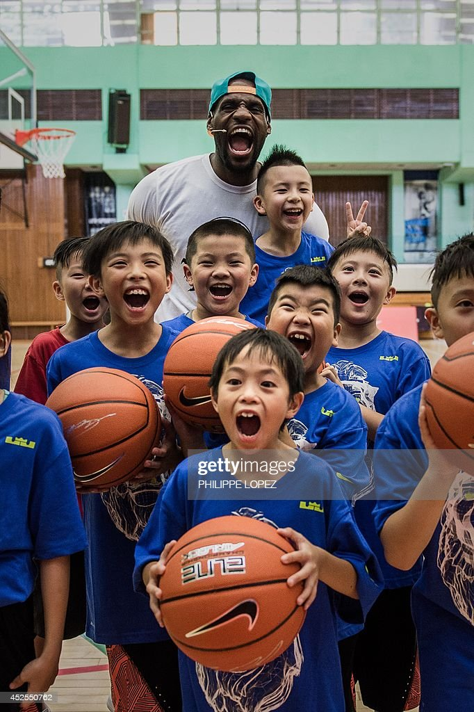 NBA professional basketball player LeBron James (top) poses during a promotional event with children and their fathers in Hong Kong on July 23, 2014. James began his tour of China on July 21 and will also visit two cities in Taiwan. AFP PHOTO / Philippe Lopez