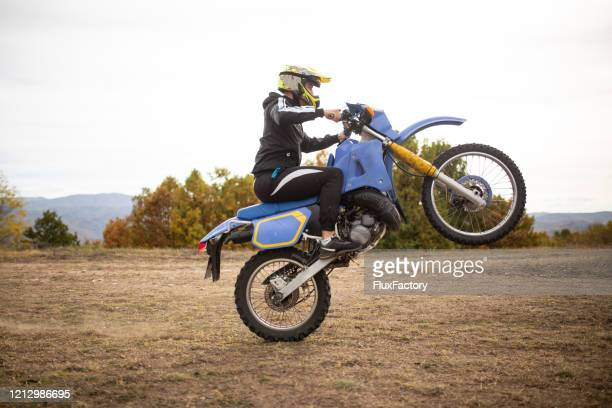 professional bike rider doing a wheelie - stunt stock pictures, royalty-free photos & images