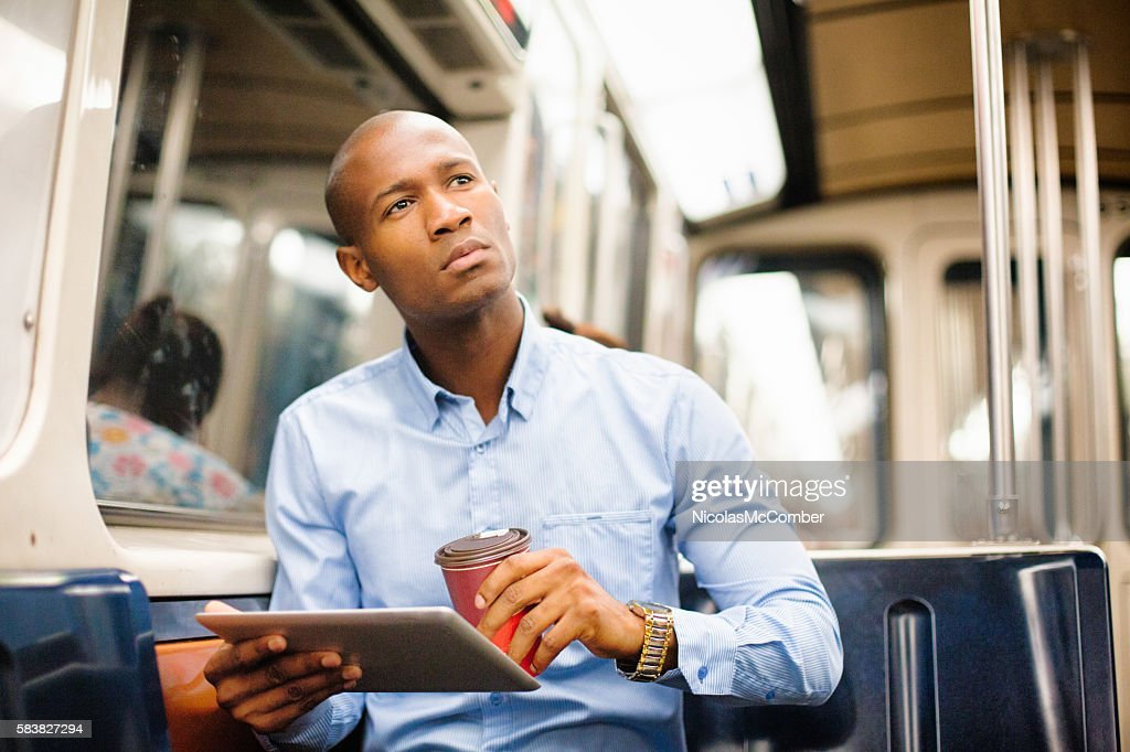 Professional black man distracted by game on subway checks location : Stock Photo