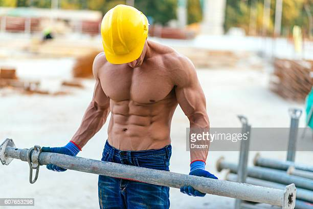 Professional body builder on construction site with heavy load