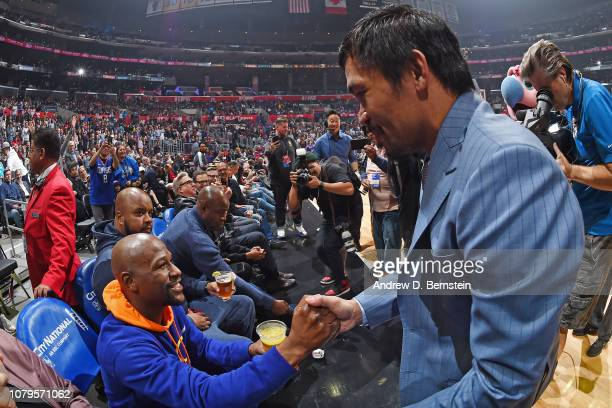 Professional Boxers Floyd Mayweather and Manny Pacquiao greet each other during the game between the Charlotte Hornets and LA Clippers on January 8...