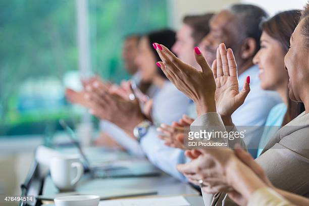 Professional business people applauding speaker at seminar or conference