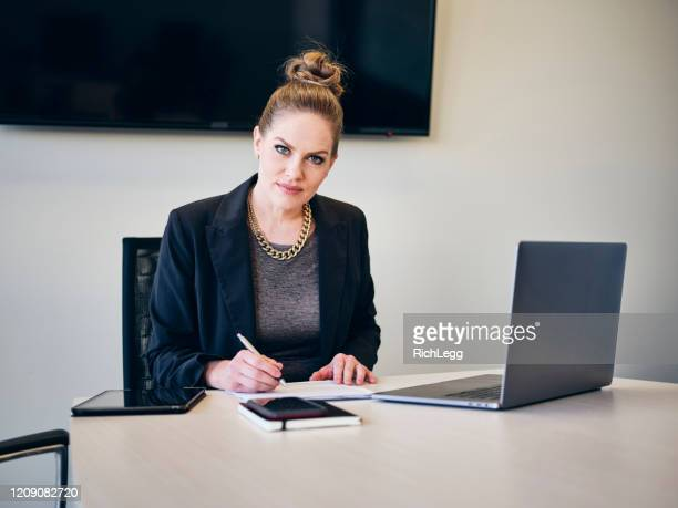 professional businesswoman in an office - rich_legg stock pictures, royalty-free photos & images