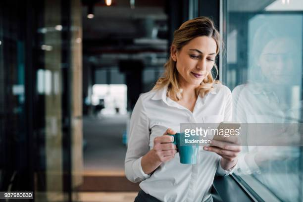 professional businesswoman texting - coffee break stock pictures, royalty-free photos & images