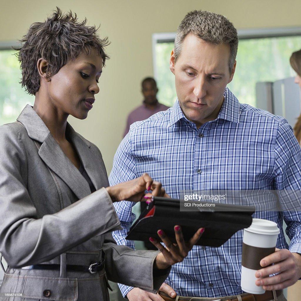 Professional businesswoman using digital tablet to instruct employee : Bildbanksbilder