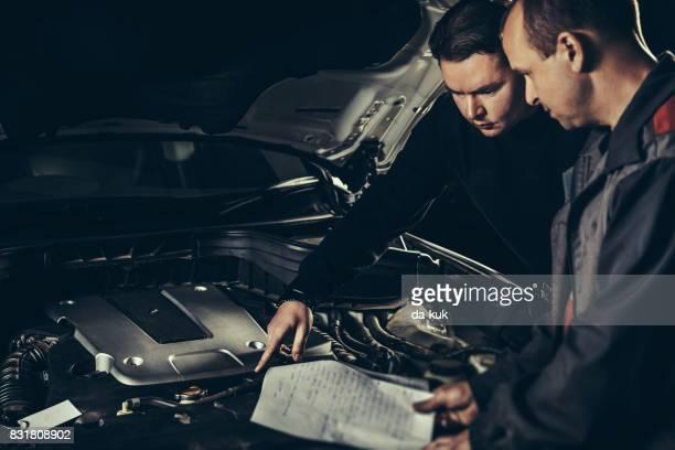Professional car mechanics repairing a car in auto repair shop