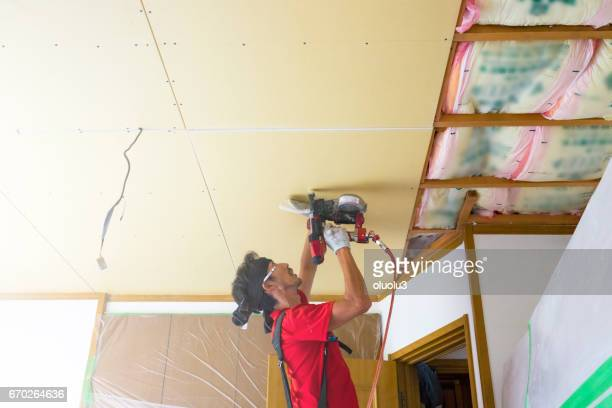 Professional carpenter is fixing the ceiling