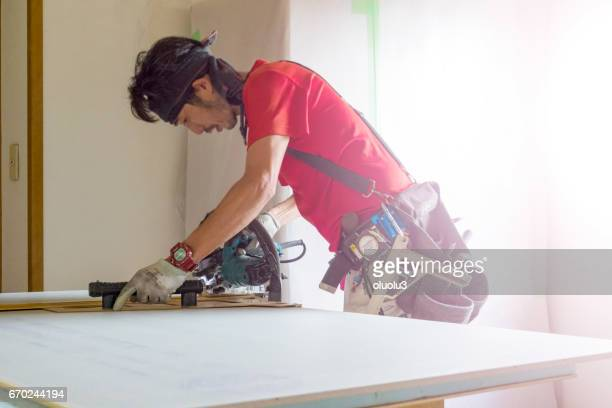 Professional carpenter measures the length of the board and cuts it