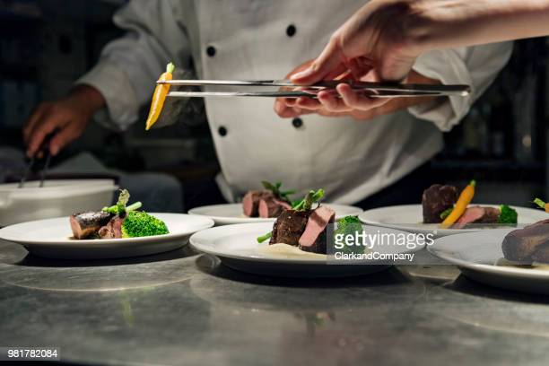 professional chef at work in a busy kitchen getting ready for service - food and drink stock pictures, royalty-free photos & images