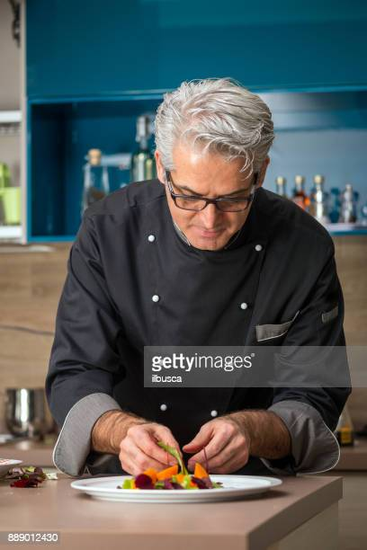 professional chef preparing meal in private house: garnishing pork roast dish - garnish stock pictures, royalty-free photos & images