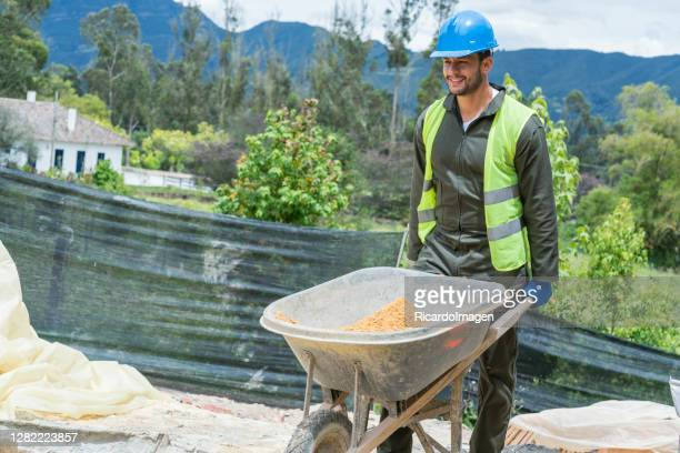 a professional construction worker works with the wheelbarrow wearing a reflective vest and a protective helmet. - general view stock pictures, royalty-free photos & images