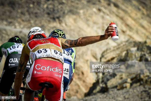 Professional Continental team Cofidis' Loic Chetout asks for water during the third stage of the cycling Tour of Oman between the German University...