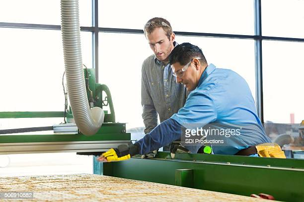 Professional craftsmen using industrial router to engrave wood in workshop