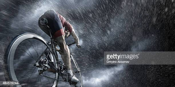 professional cyclist under stormy sky - endurance stock photos and pictures