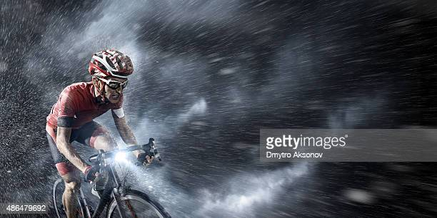 Professional cyclist under stormy sky