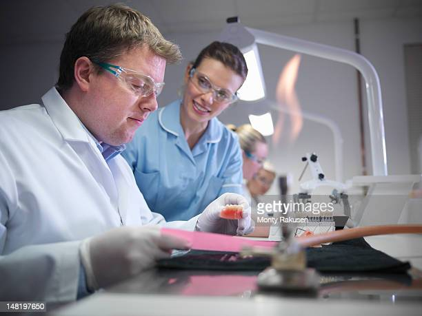 professional dentist and apprentice in dental laboratory - bunsen burner stock pictures, royalty-free photos & images