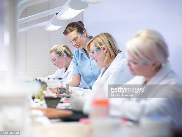 Professional dentist teaching apprentices in dental laboratory