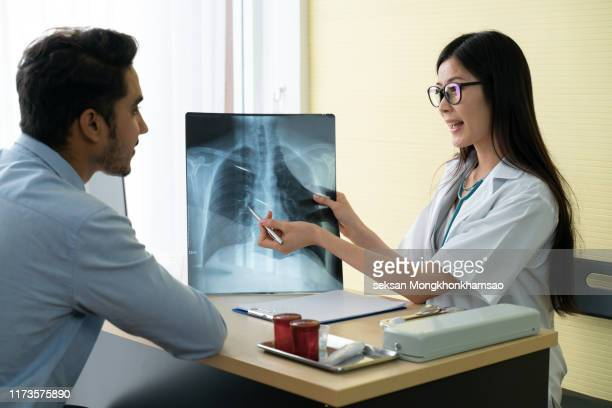 professional doctor and radiologist giving a consultation to his patient, he is examining and x-ray image and pointing - x ray image ストックフォトと画像