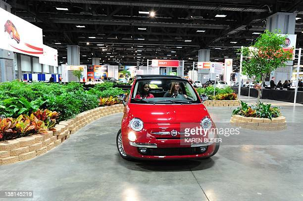 A professional driver takes a potential car buyer for a test ride in a Fiat 500 at the Fiat Ride on February 2 2012 at the 2012 Washington Auto Show...