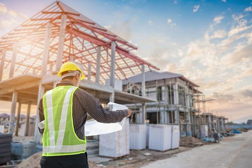 Professional engineer architect worker with protective helmet and blueprints paper at house building construction site 1041465228