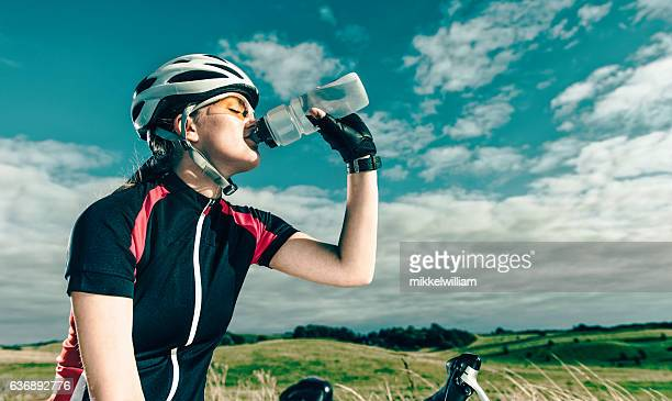 Professional female bike rider drinks water during break