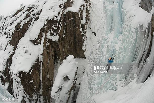 A professional female climber ice climbing a frozen waterfall at Ouray Ice Park in Ouray, Colorado.