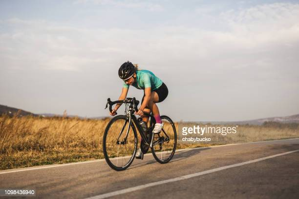 professional female cyclist on the road - racing bicycle stock pictures, royalty-free photos & images