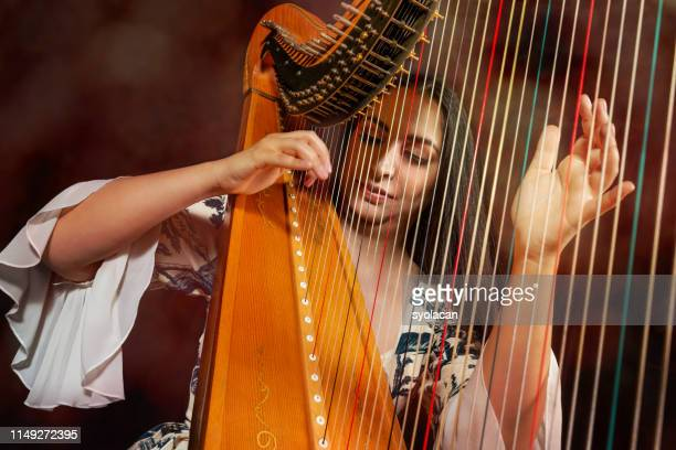 professional female harpist during performance - syolacan stock pictures, royalty-free photos & images