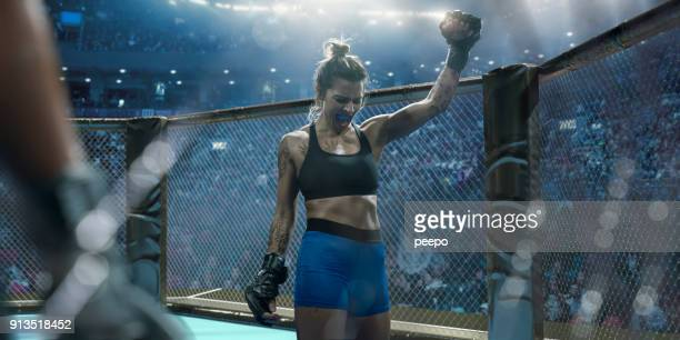 professional female mixed martial arts fighter raising fist in victory - coraggio foto e immagini stock