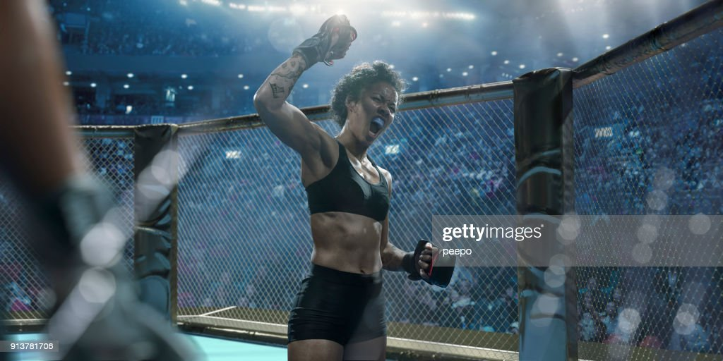 Professional Female Mixed Martial Arts Fighter Raising Fist In Victory : Stock Photo