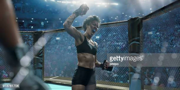 professional female mixed martial arts fighter raising fist in victory - mixed martial arts stock pictures, royalty-free photos & images